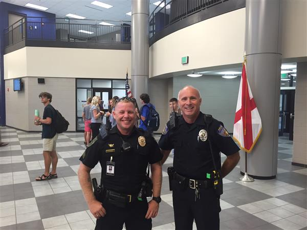 Two SRO officers smiling in lobby of James Clemens High School