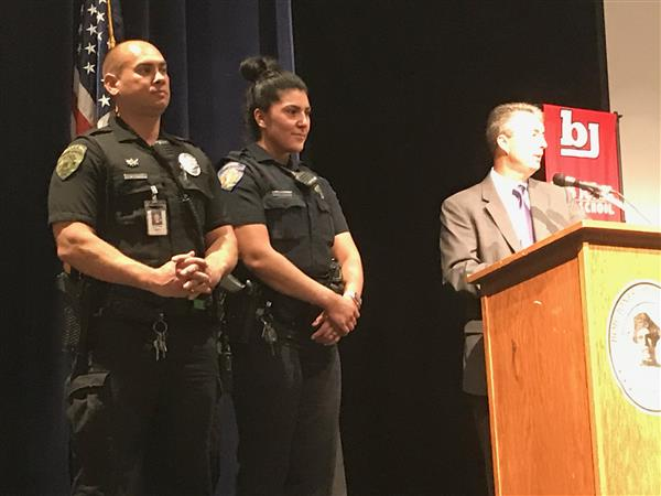 Two officers on high school stage being recognized by Alabama attorney general Steve Marshall.