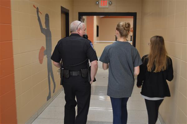 SRO officer talking with students in school hallway
