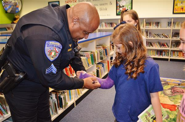 Officer signs the arm cast of student in school library