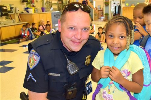 Police officer with PreK student in classroom