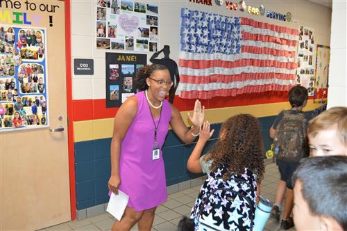 Teacher  high fiving a student in hallway at Rainbow Elementary