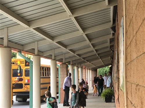 Principal greeting students in bus line at Horizon Elementary