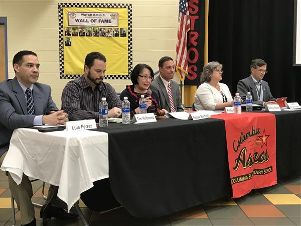 Board members lined up on table in public hearing at Columbia Elementary
