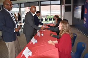 student panel greeting guests with handshakes