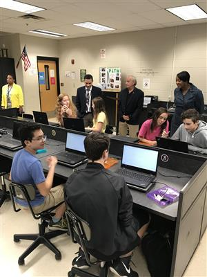 Guests hovering over students working on computers in the CodeSpace class at Discovery Middle