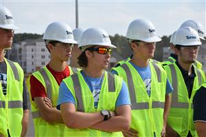 Students in hard hats listening to construction manager