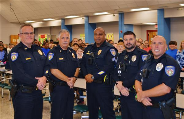 Group of officers with chief at a Too Good For Drugs graduation in an elementary school