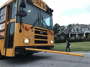 Schoolbus with stoparm extended along a neighorhood street bus stop