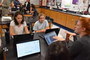 several students collaborating around computers in the Biomed internship class
