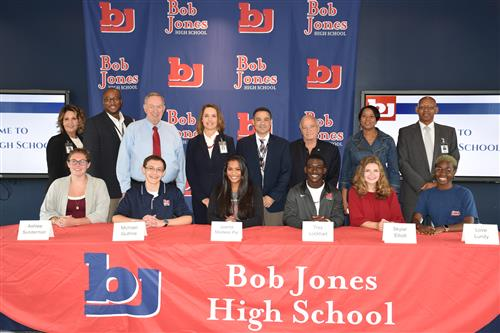 Group photo of students and lawmakers and board members at table in Bob Jones High School