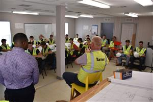 Students at table inside construction trailer getting a briefing from Turner Universal contractors