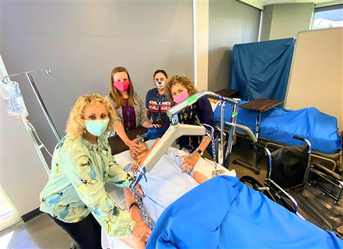Four Bob Jones health sciences teachers circled around a robotic patient in a classroom