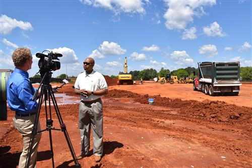 Interim Superintendent Eric Terrell being interviewed by TV reporter as equipment works in background