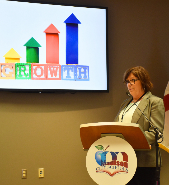 Photo of Dorinda White Going Over Growth Charts at Podium.