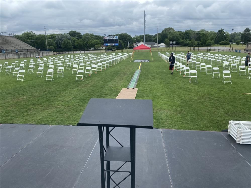Wide angle photo of empty chairs for graduating seniors in stadium