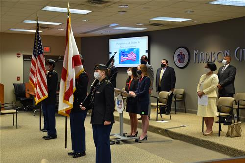 color guard at attention in front of board members in masks