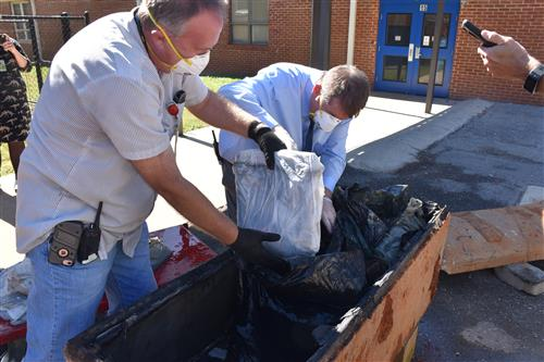 Two school officials in masks and gloves retrieving items from time capsule