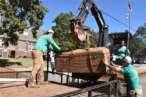 Time capsule being hoisted from ground and loaded on truck