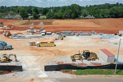 Aerial view of construction site showing site leveling and brick work so far.