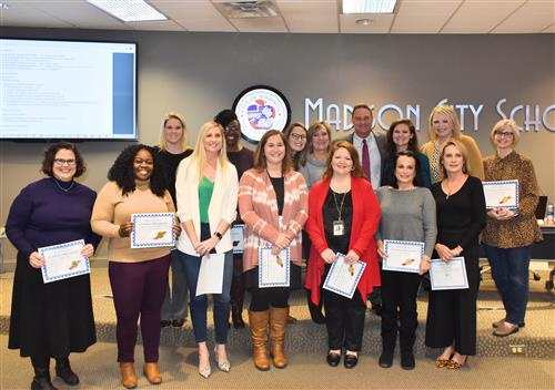 13 National Board Certified Teachers with certificates in front of the Madison City Board of Education