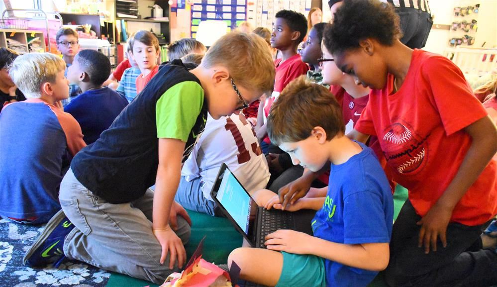 Students collaborate in a STEM excercise tied to the Alabama-Auburn football rivalry