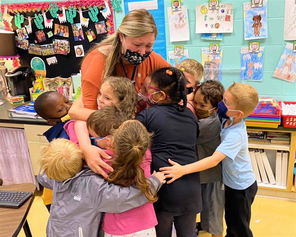 Teacher surrounded by kids hugging her