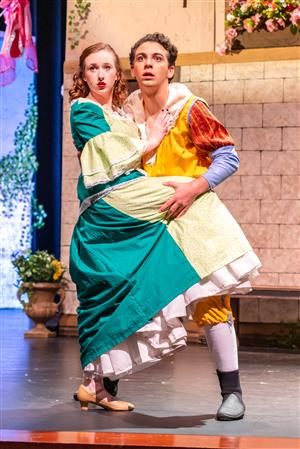 Male and female actors dance in costume on stage