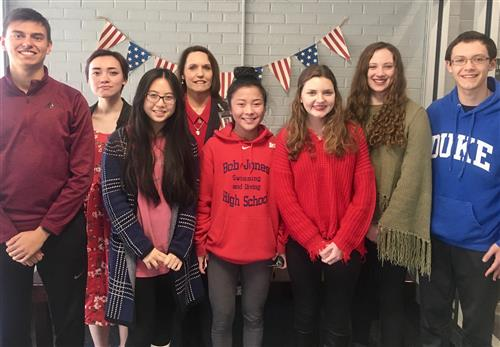 7 students with Principal Sylvia Lambert standing with flags in background