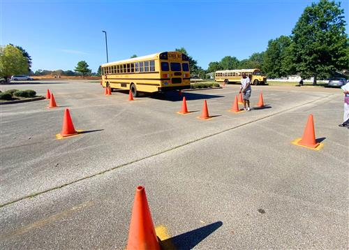 bus driving through safety cones in a parking lot
