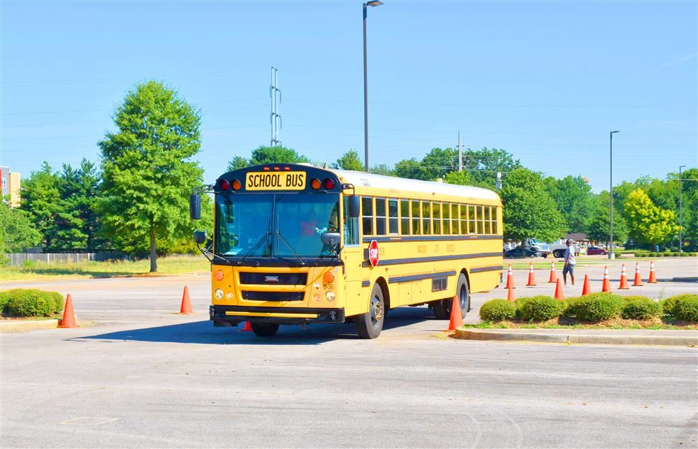 Bus maneuvering through traffic cones in stadium parking lot