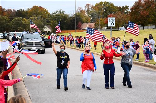 Four Columbia Elementary teachers leading parade carrying flags
