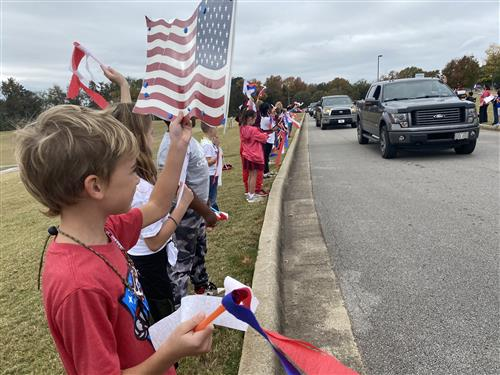 Students lining parade route with flags