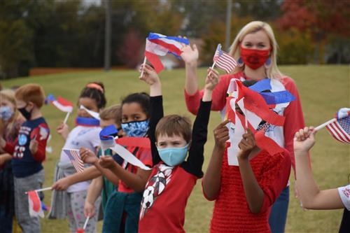 Kids lining parade route holding flags with teacher