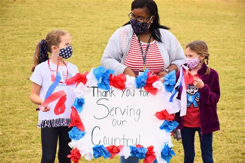 Teacher with two students holding sign thanking veterans for serving our country