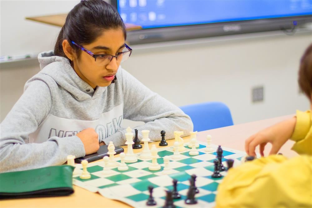 Girl student concentrating over chess board with opposing player in foreground