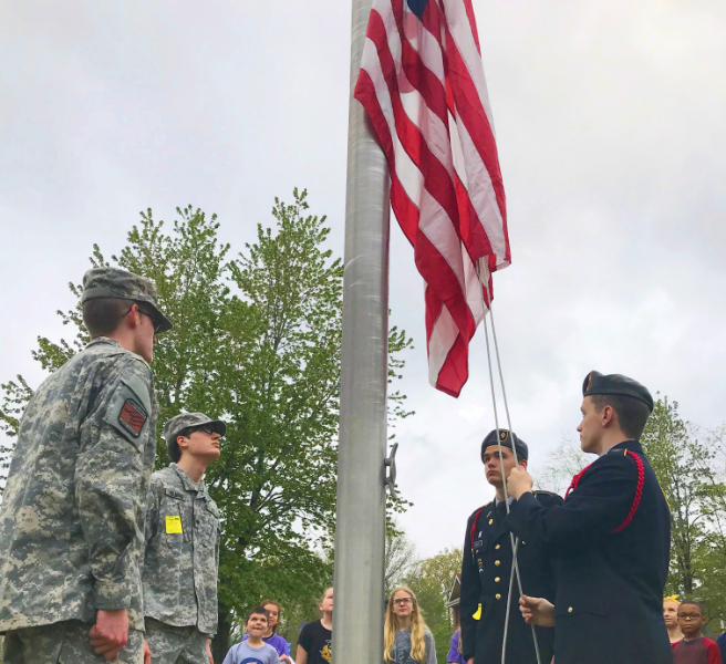 ROTC cadets lowering a United States flag at Heritage Elementary