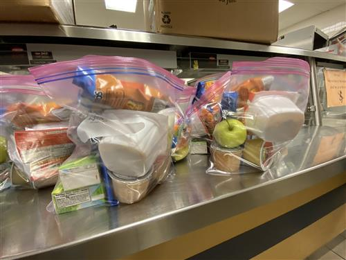 Prepackaged lunches in clear bags awaiting delivery