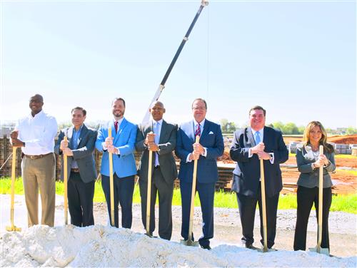 Board members and superintendent standing with shovels at construction site