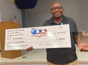 David Jones is the District Staff Member of the Year holding a five thousand dollar check. He works at Heritage Elementary