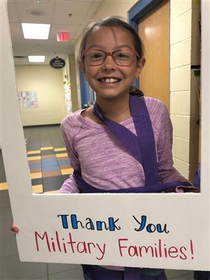 student in framed sign thanking military families