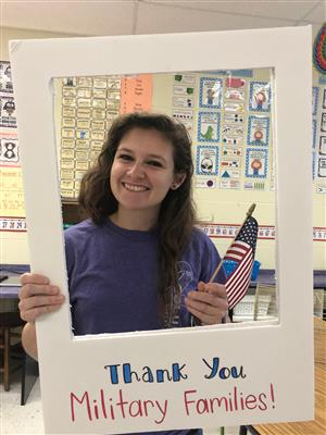 teacher holding flag and thank you sign to military families