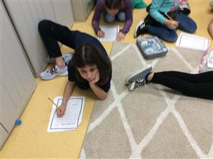 students spread across on floor writing thank you letters to military families