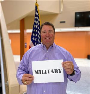 Principal Shannon Brown at Liberty Middle in purple shirt holding sign thanking military