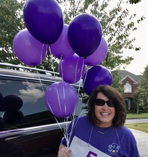 Teacher holding purple balloons
