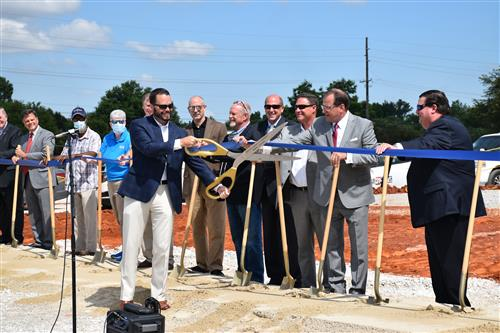 Tim Holtcamp cuts ribbon at construction site with officials looking on