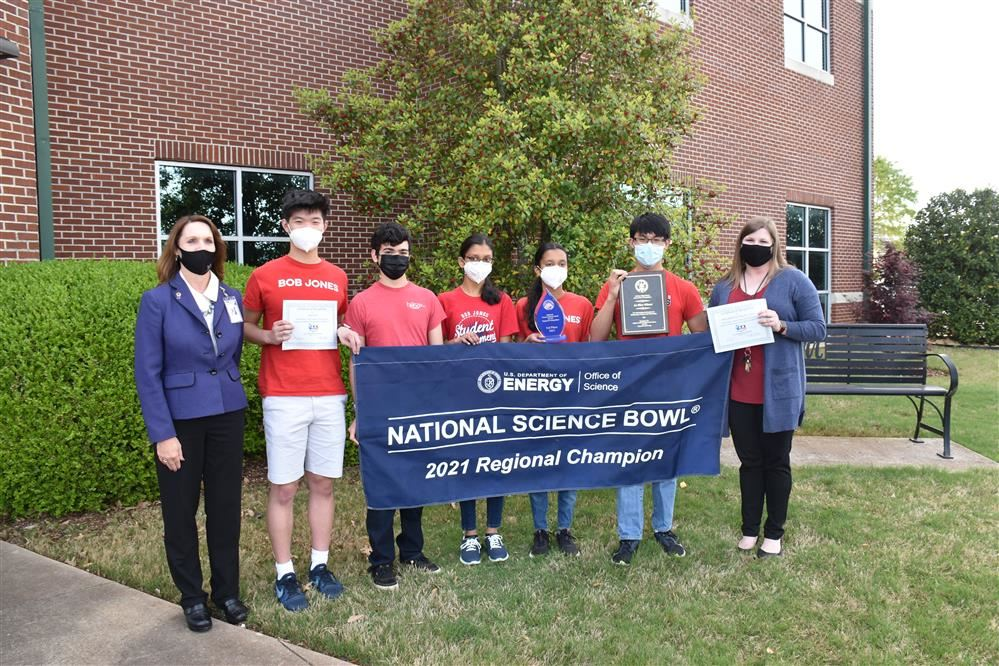 Science bowl winners standing with banner outside of central office