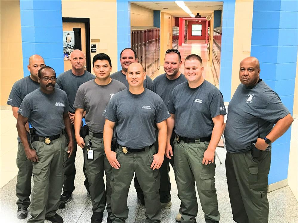 Eight SROs in uniform in a group photo in a school hallway